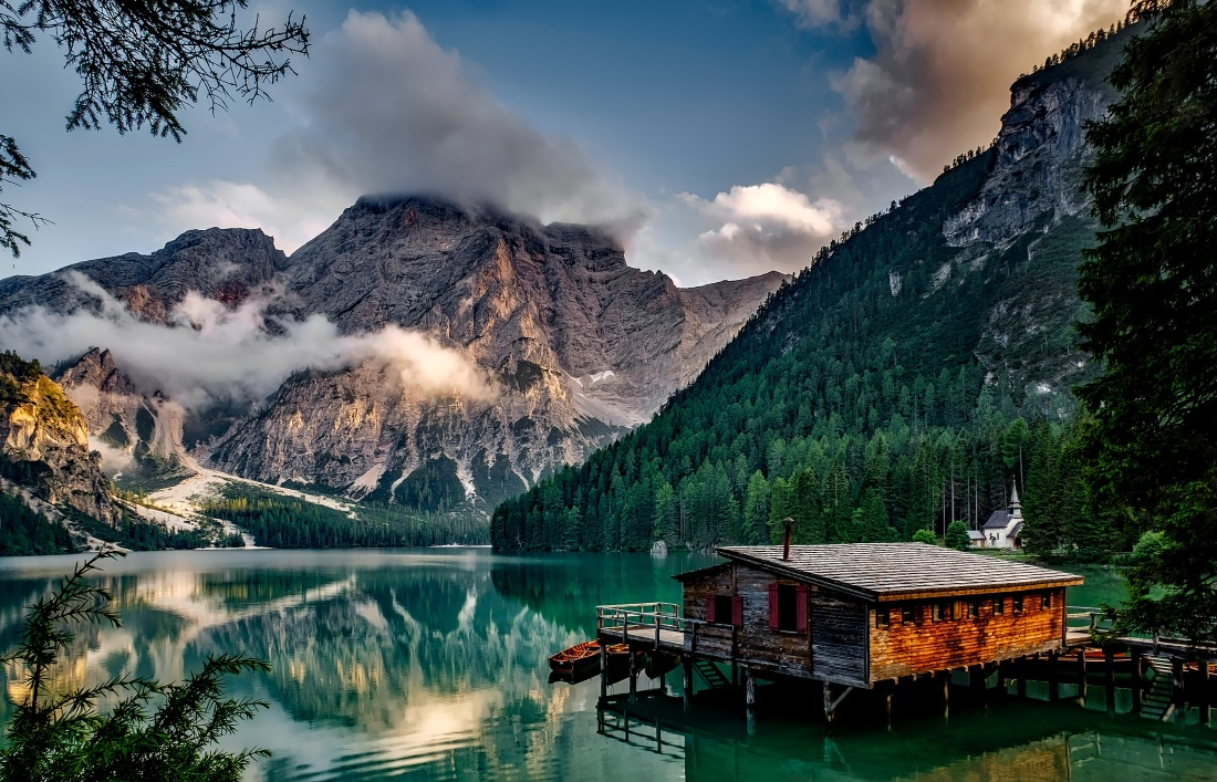 Mountain lake with rustic cabin, mountains, and classic white church around the lake.